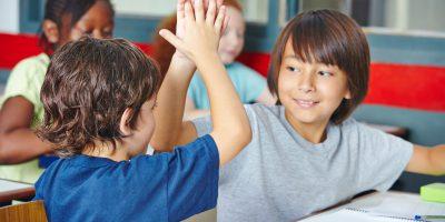 Zwei glückliche Schüler geben sich High Five im Unterricht